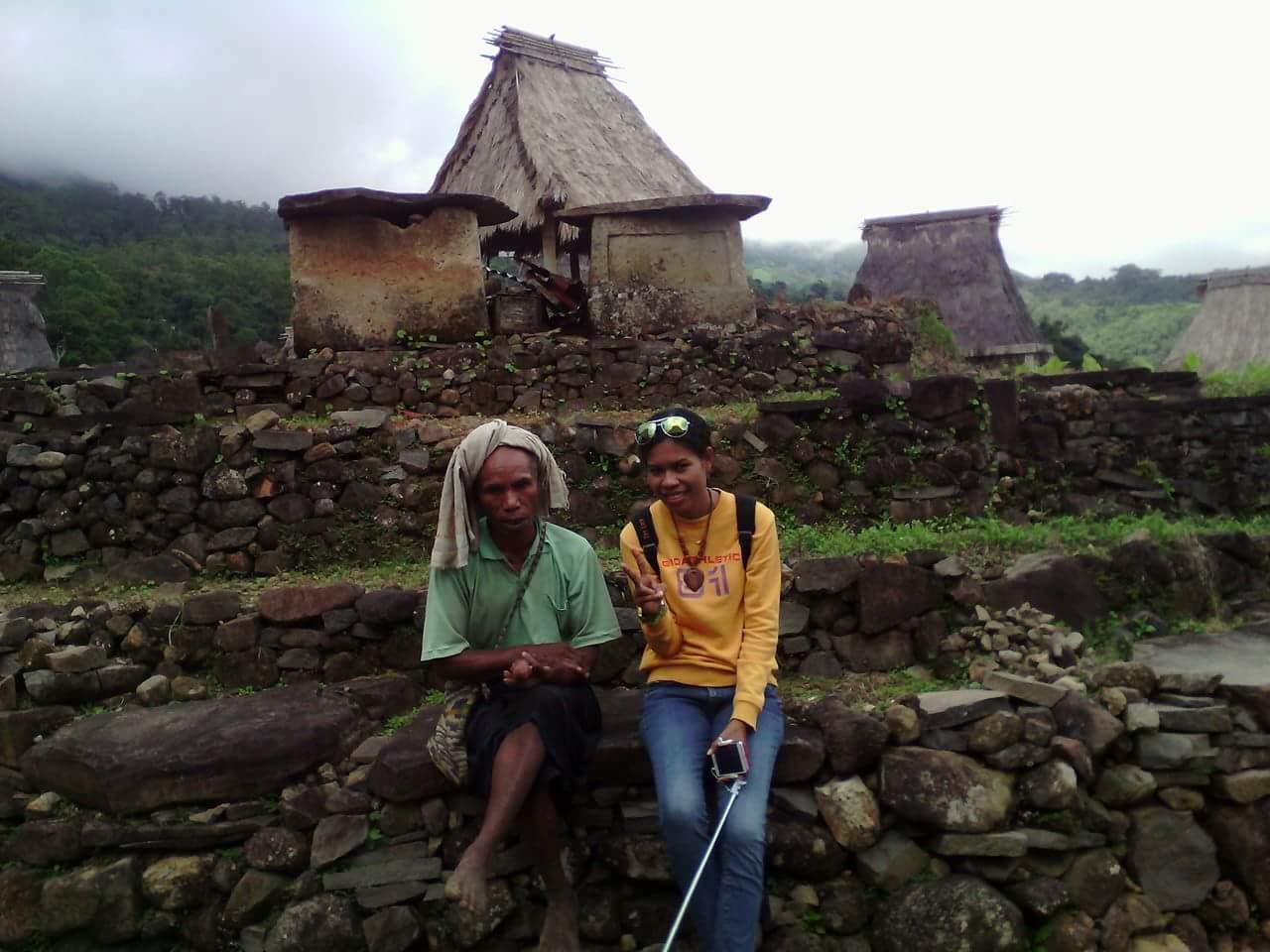 Seorang wisatawan lokal foto bersama bapak  Aloysius Leta, tokoh adat dan seniman lokal dengan back ground rumah penyimpanan benda – benda peninggalan leluhur dan tempat dilakukan upacara adat.